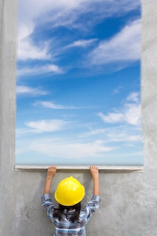 Niña que sostiene las herramientas de enyesado que renuevan una casa. con pintura azul cielo nubes