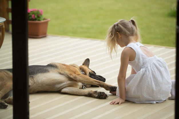 Niña que sostiene la pata de los perros que se sienta cerca de la mascota en el porche