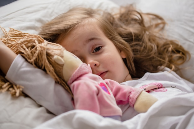 Niña se queda dormida en la cama con muñeco blanco suave