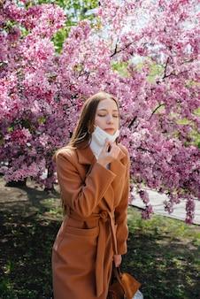 Una niña se quita la máscara y respira profundamente después del final de la pandemia en un soleado día de primavera, frente a los jardines en flor. protección y prevención covid 19.