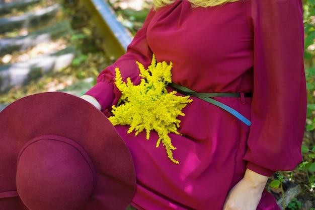 Niña con ramo de flores amarillas y sombrero de cereza