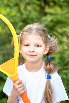 Una niña con una raqueta de tenis para niños en sus manos