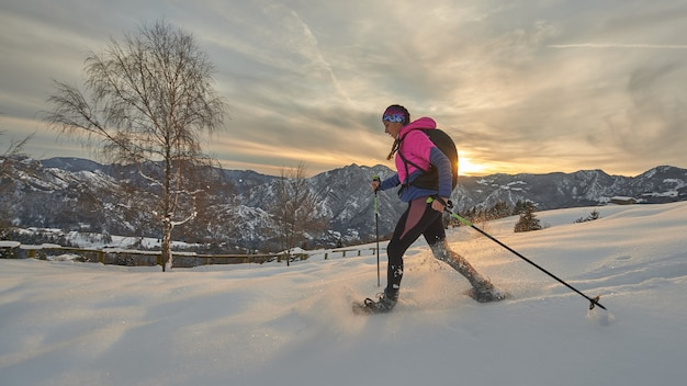 Una niña con raquetas de nieve en un hermoso atardecer de invierno
