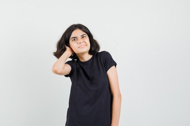 Niña rascándose la cabeza en camiseta negra y mirando pensativo, vista frontal.