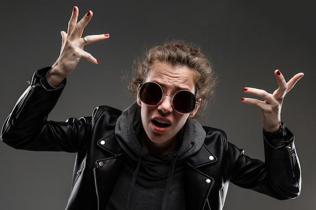 Niña con rasgos faciales ásperos, cabello castaño, manicura brillante, bicicleta gris, chaqueta negra, gafas de sol con las manos y desconcertante