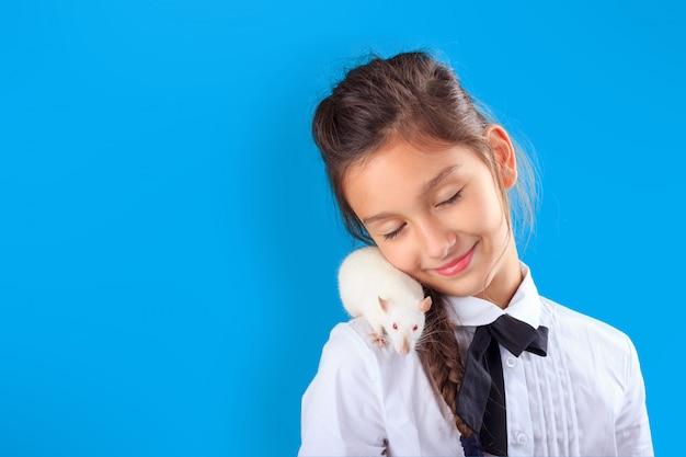 Niña con rata mascota blanca en su hombro