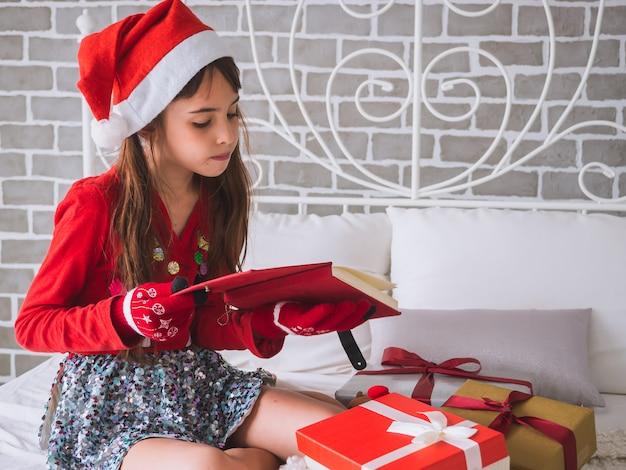 La niña recibió el libro rojo como regalo el día de navidad.
