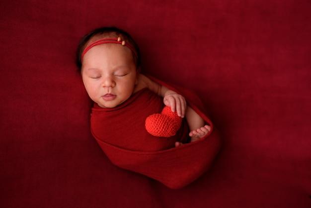 Niña recién nacida durmiendo sobre un paño rojo en una envoltura roja