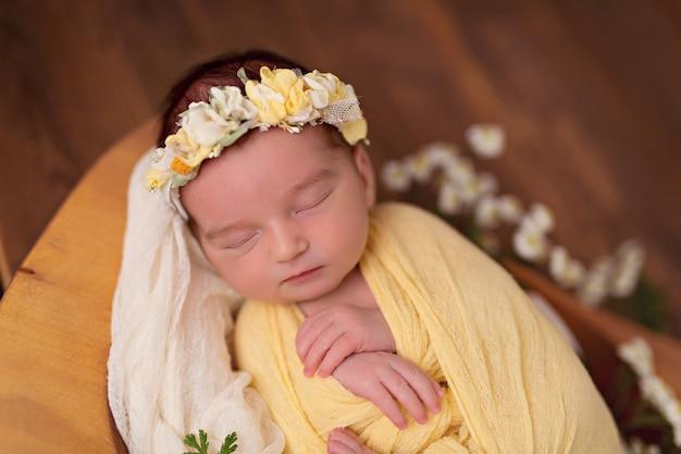 Niña recién nacida en un sinuoso amarillo duerme en una canasta con flores.