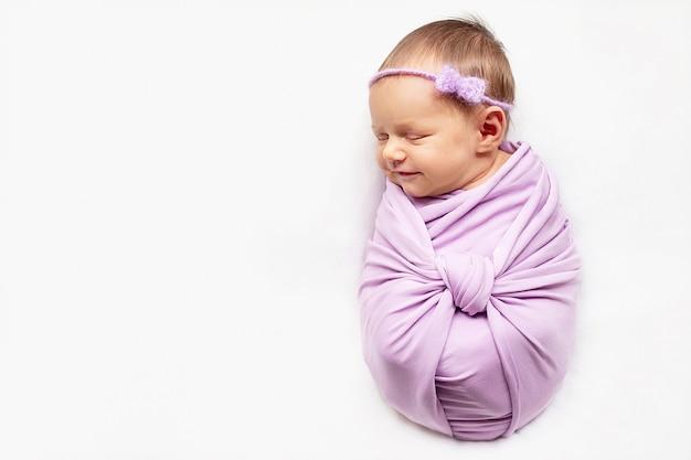 La niña recién nacida sonriente está durmiendo en el fondo blanco