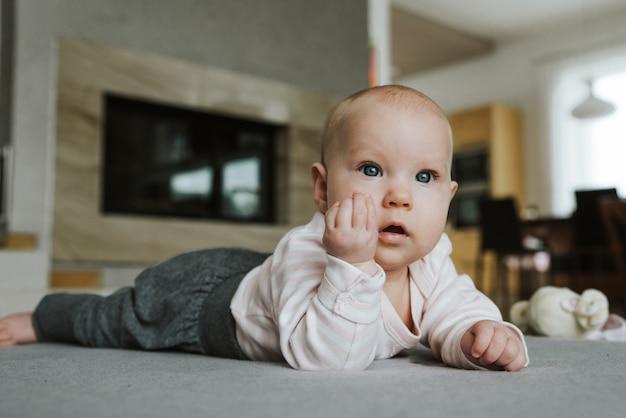 Niña recién nacida en el suelo con mano gesto italiano