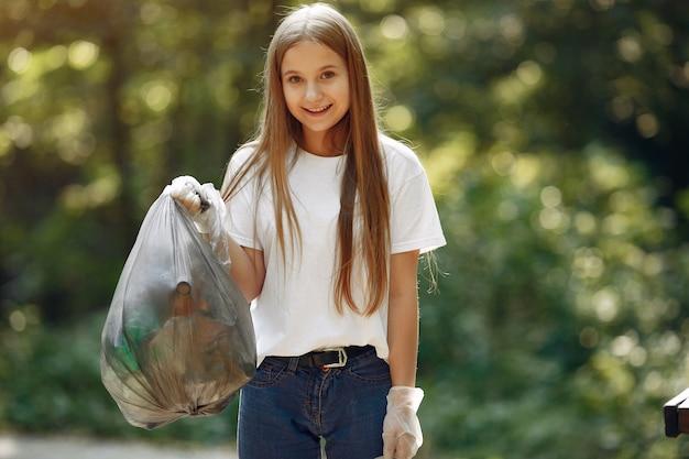 Niña recoge basura en bolsas de basura en el parque