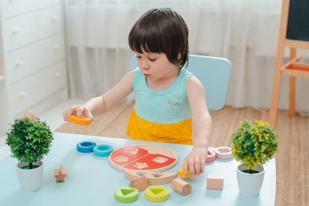 Niña recoge una pirámide de madera sin pintar. juguetes seguros para niños de madera natural.