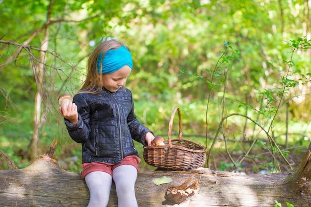 Niña recogiendo hongos en un bosque de otoño