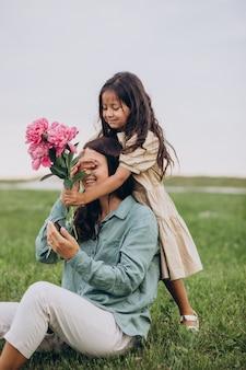 Niña regalando flores a su madre.