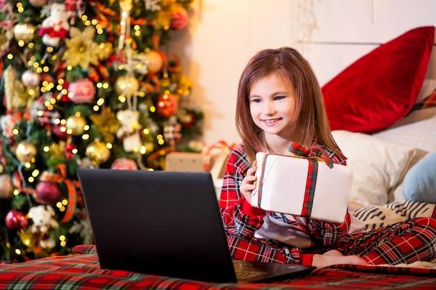 Una niña con un regalo de navidad en sus manos se sienta en pijama en la cama frente a una computadora portátil en el contexto de un árbol de navidad.