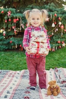 Niña con regalos cerca de un árbol de navidad, navidad en julio en la naturaleza