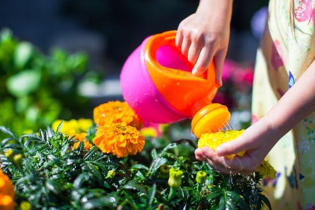 Niña regando flores con una regadera