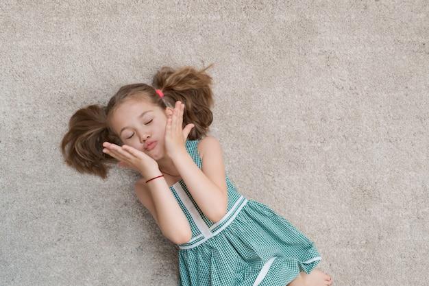 Niña relajada tirada en el suelo en el interior y sonriendo