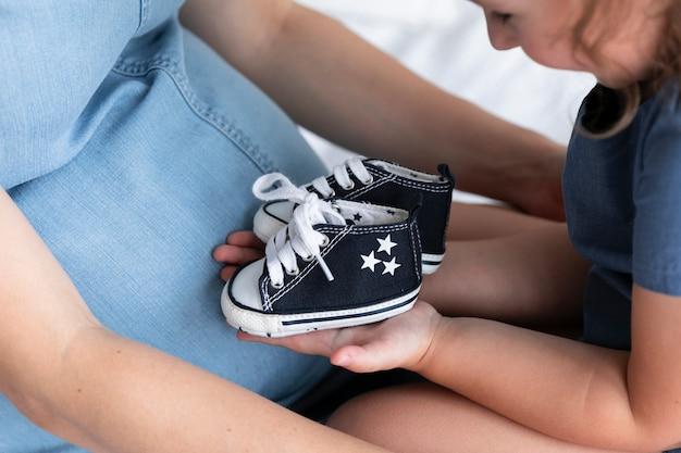 Niña revisando sus zapatos de hermano pequeño