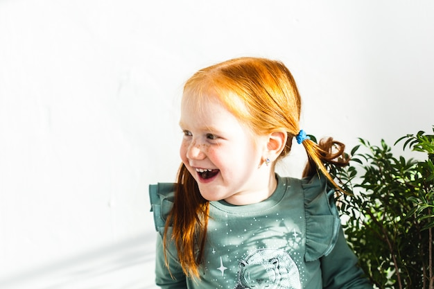 La niña se ríe, juega con su hermana, su familia, sostiene flores y hojas en sus manos.