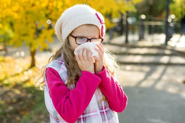 Niña con rinitis fría, temporada de gripe, alergia nariz que moquea