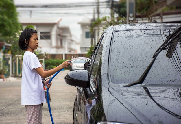 Niña rociando un coche con una manguera de agua lavar un coche