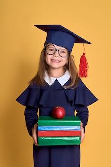 Niña en ropa académica con libro