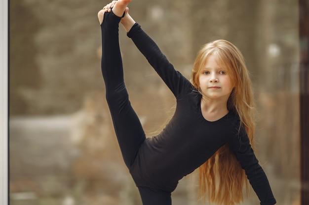 Niña en ropa deportiva negra se dedica a la gimnasia