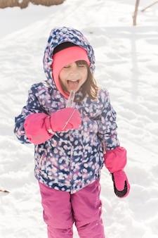 Niña en ropa de invierno prueba el hielo