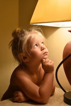 Una niña sin ropa mira la luz de la lámpara y sueña en la habitación por la noche.