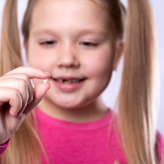 Niña en rosa sostiene un diente de leche caído
