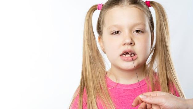 Niña en rosa sostiene con un hilo en un diente de leche.
