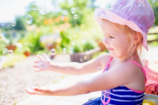 Niña rubia de 3 años en un sombrero rosa y traje de baño azul con baño en el patio y jugando con burbujas.