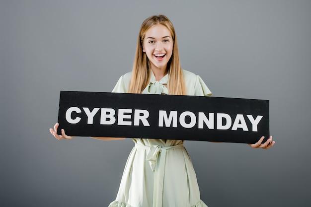 Niña rubia alegre sonriente con cyber lunes signo aislado sobre gris