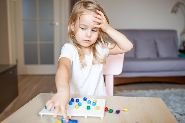 Niña rubia en una camiseta blanca jugando con mosaico multicolor plástico en casa o preescolar. concepto de educación temprana.