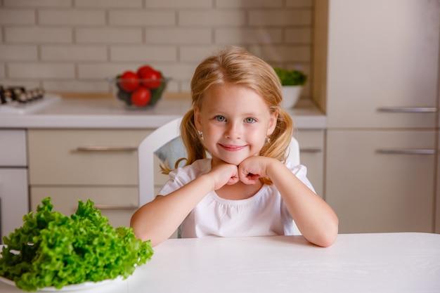 Niña rubia comiendo verduras en la cocina