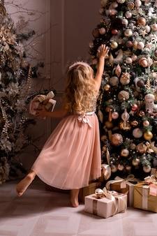 Niña rubia decora el árbol de navidad en un hermoso interior