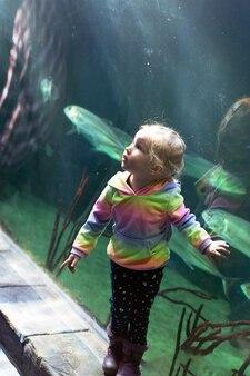 Niña rubia emocionada en acuario. los niños pequeños están viendo peces en el oceanario. actividad de ocio, formato vertical. bajo el agua