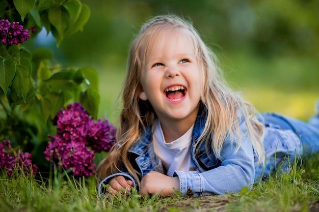 Niña rubia se encuentra cerca de las flores de color lila en la hierba verde y sonrisas