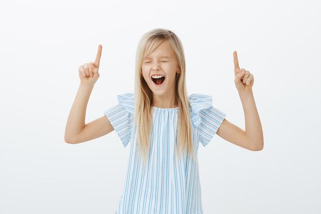 Niña rubia enérgica desobediente, levantando los dedos índices y apuntando hacia arriba, gritando o gritando en voz alta con los ojos cerrados, siendo desobediente mientras exige comprar juguetes nuevos, parada sobre una pared gris