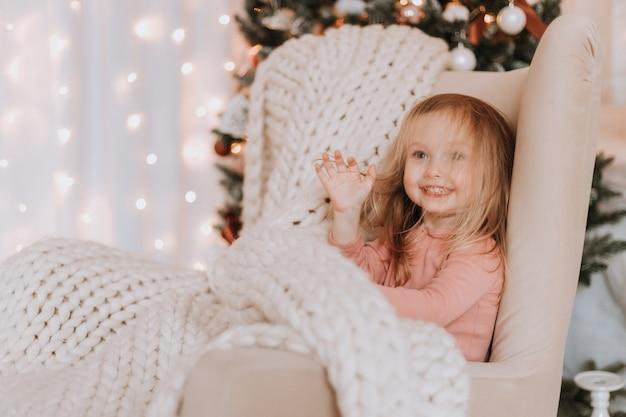 Niña rubia envuelta en una gran tela escocesa de punto está sentada en una silla junto al árbol de navidad