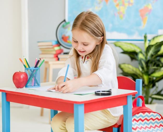 Niña rubia escribiendo trabajo de clase en el aula de la escuela