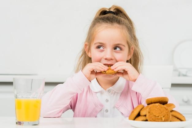 Niña rubia con galletas y zumo de naranja