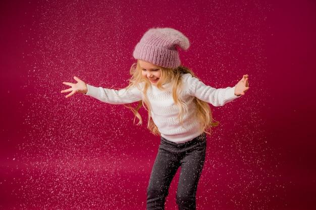 Niña rubia con gorro de punto y suéter juega con la nieve