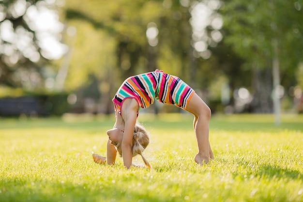 Niña rubia haciendo gimnasia en un césped verde en el verano