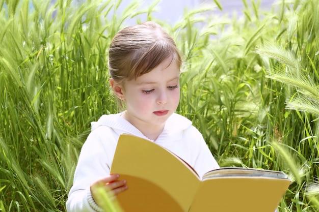 Niña rubia leyendo libro entre espigas verdes prado jardín