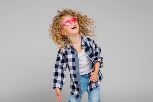 Niña rubia niña en gafas rosa sonriendo