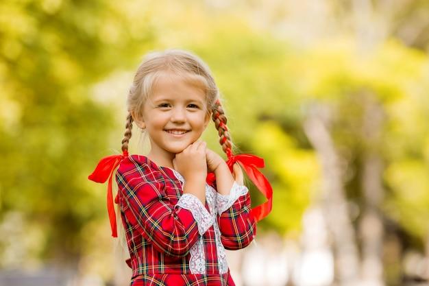 Niña rubia primer grado vestido a cuadros rojos sonriendo en la calle