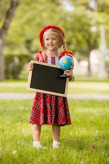 Niña rubia de primer grado en vestido rojo y boina sosteniendo un tablero de dibujo vacío y globo